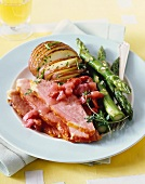 Roast ham with green asparagus a baked potato