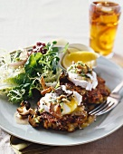 Mushroom cakes with poached eggs and Hollandaise sauce and a side salad