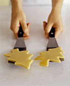 Two Christmas Tree Shaped Sugar Cookies on Spatulas