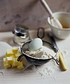 Baking Ingredients: Egg, Flour, Butter with Sifter