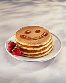 Pancakes with a Maple Syrup Smiley Face; Fresh Strawberries