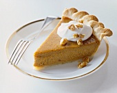 Slice of Pumpkin Pie with Whipped Cream and Chopped Walnuts