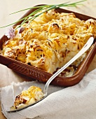 Savory Bread Pudding with Onions and Cheese; In Baking Dish with Scoop Removed