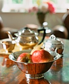 Apples in a silver bowl with a teapot in the background