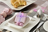 A breakfast place setting with a wrapped present and pink Easter decoration