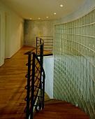 Geschwungene Wand aus Glasbausteinen in einem beleuchteten Treppenraum