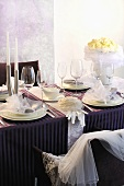A festively laid wedding reception table with purple table runners and decorative bows