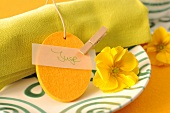 A green napkin on a plate with a name tag and a yellow flower