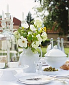 A bunch of white flowers on a table laid in a garden