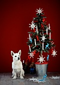 A small Christmas tree decorated with crocheted snowflakes and a dog sitting next to it