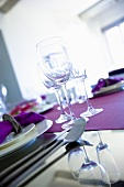 Wine glasses on a purple table runner, photo taken at an angle