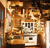 A country house kitchen with baskets, dried chilli peppers and corn cobs hanging from the ceiling,