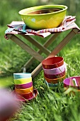Colourful bowls in the grass and a large bowl on a folding stool