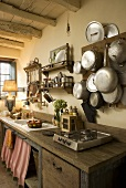 A kitchen counter with a rustic wooden work surface and pots and pans hanging on a wooden board