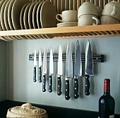 Cups and plates on a shelf above a magnet knife holder