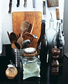A pepper mill, a jar of salt, brown sugar in a shaker, wooden spoons etc