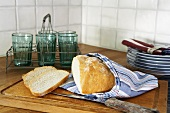 Sliced white bread on a wooden board with glasses and plates behind
