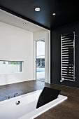 Schwarz-weisses Designer Bad mit Badewanne im Boden eingelassen und Handtuchtrockner an schwarzer Wand
