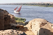 View over some ruins to a boat with red and white sails on the River Nile, Egypt