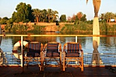 Evening on a boat with wicker chairs in front of the railing and a view of the jungle from the River Nile, Egypt