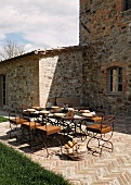 A table laid on a terrace in front of a Mediterranean country house and a stone floor with a herring bone pattern