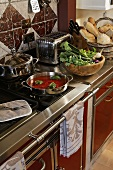 An elegant, stainless steel kitchen counter with food on the hob