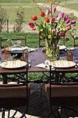 Bunter Tulpenstrauss auf gedecktem Tisch im Freien