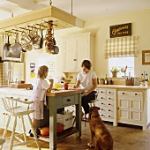 A family and a dog sitting at a kitchen island in the kitchen of a country house