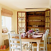 A dining table laid in front of an open glasses cabinet