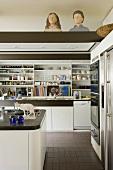 weiße Einbauküche mit offenen Regalschränken und Holzbüsten auf abgehängter Decke
