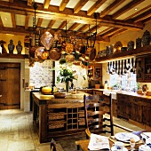 Copper pans hanging above an old kitchen counter in the kitchen of an English country house with a wood beam ceiling