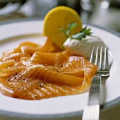 Slices of salmon on a plate with a fork