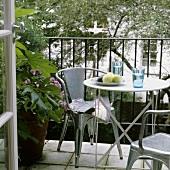 Metallstühle um Bistrotisch auf Balkon und Blick in Garten