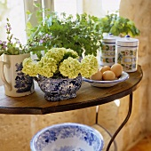 Bunches of herbs and flowers in porcelain jars on a side table
