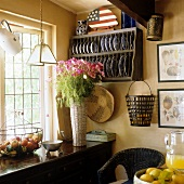 A corner of a kitchen with a plate rack and a bunch of flowers on a wooden shelf in front of the window