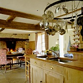 An open-plan kitchen in a country house with a dining area in front of a fireplace