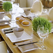 Oriental place settings at a wooden table with wine glasses and fresh herbs