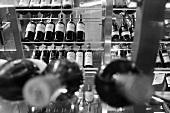 Glasregal mit ausgestelltem Wein in schwarz-weiss Aufnahme