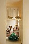 Ablagen mit Glasgefässen in schmaler Öffnung und Blick auf antiken Sessel