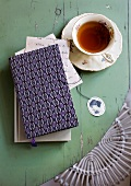 A cup of tea next to a book with a patterned cover on a green wooden surface