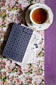 A cup of tea next to a book with a patterned cover on paper with a floral design