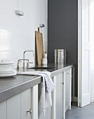 A grey kitchen counter with a sink and a cupboard underneath