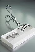 An eyelash curler and fake eyelashes