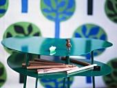 Spielzeugfigur und Buntstifte auf geschwungenem Ablagen Tisch aus grün glänzendem Metall