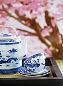 A detail of a Japanese blue and white china cups and saucers and teapot on tray