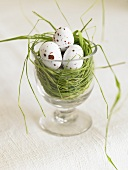 A nest in a glass with speckled eggs