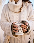 A woman in a white knitted jumper holding a mug