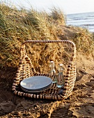 A picnic basket in the sand with a sea view