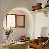 Muscheln und Wassermelone auf Ablage aus Stein unter Fenster in Alkoven im Mediterraner Küche und Gemüse auf Arbeitsplatte