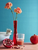 A pomegranate, pomegrante juice and carnations in a vase against a blue background